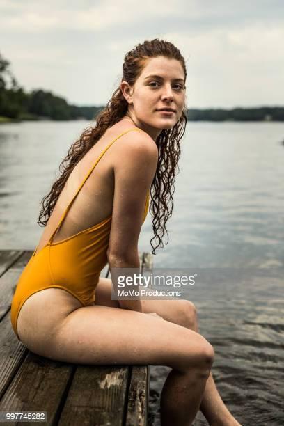young woman sitting dock at lake