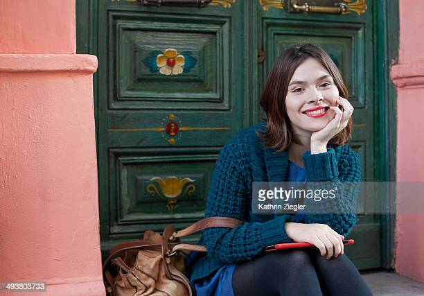 young woman sitting on doorstep, smiling