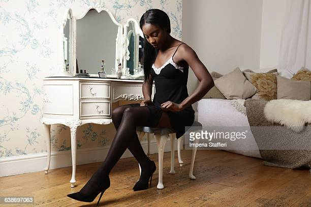 Young woman sitting on dressing table stool, putting on stockings