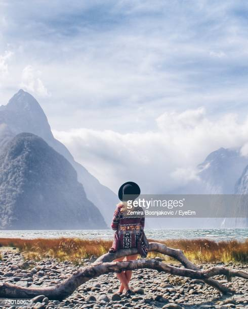 Young Woman Sitting On Driftwood At Lakeshore Against Snowcapped Mountains