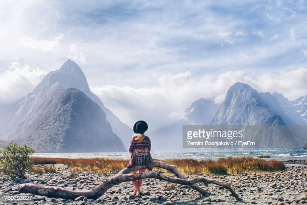 young woman sitting on driftwood at lakeshore against snowcapped mountains - new zealand bildbanksfoton och bilder