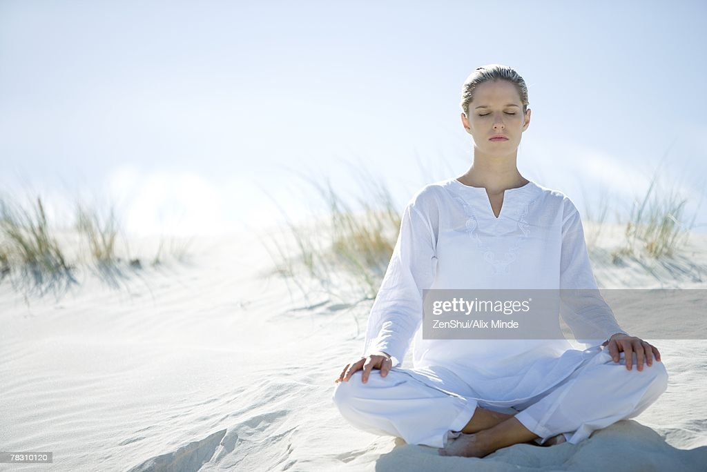 Young woman sitting on dune indian style, eyes closed : Stock-Foto