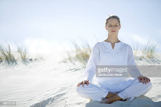 Young woman sitting on dune indian style, eyes closed