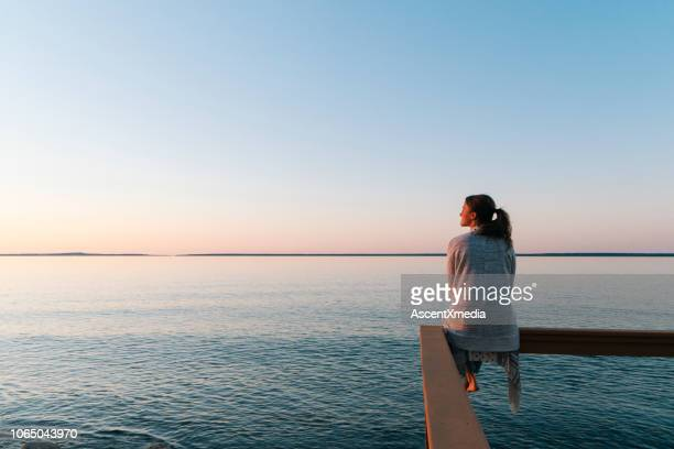 young woman sitting on edge looks out at view - sunset lake stock photos and pictures