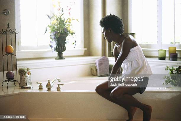 Young woman sitting on edge of bathtub