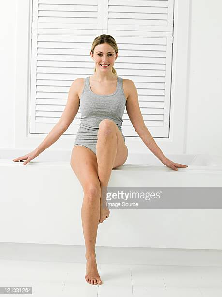 Young woman sitting on edge of bathtub with louvered door