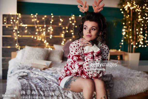 young woman sitting on edge of bed, wearing christmas jumper and antlers, thoughtful expression - christmas jumper fotografías e imágenes de stock