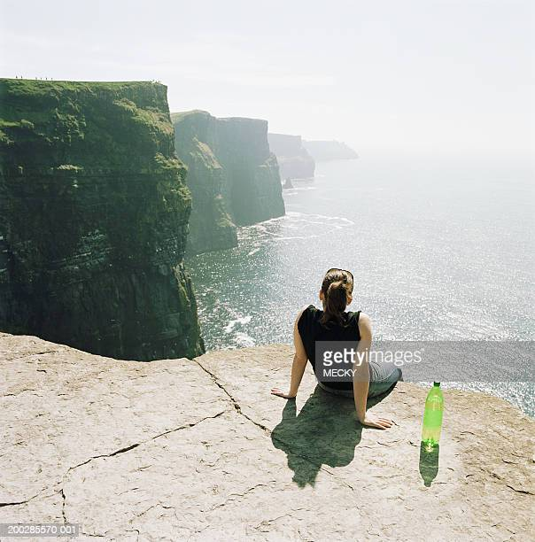 Young woman sitting on edge of cliff overlooking sea, rear view