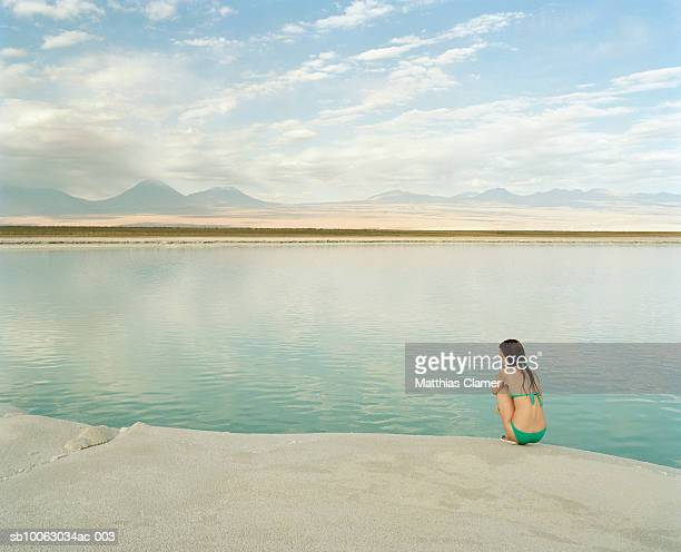 Young woman sitting on edge of salt water lagoon