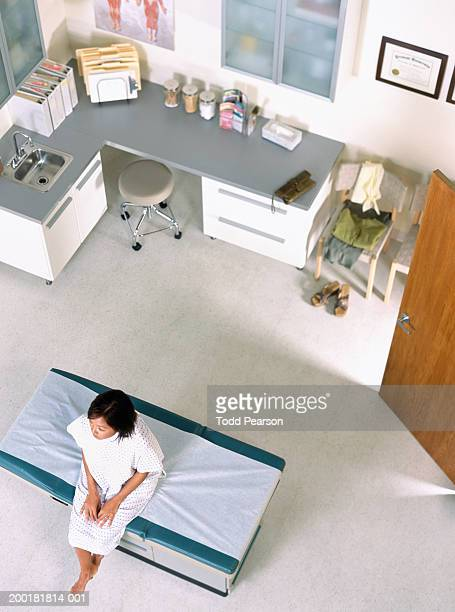Young woman sitting on exam table in doctor's office, elevated view