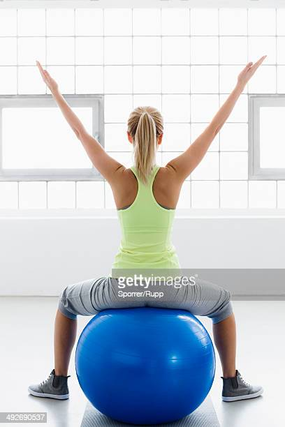 Young woman sitting on exercise ball, arms raised, rear view