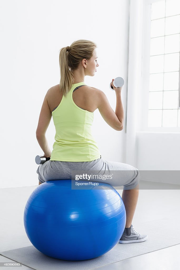 Young woman sitting on exercise ball, rear view, lifting weights : Stock Photo