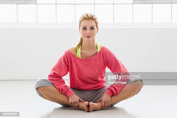 Young woman sitting on exercise mat