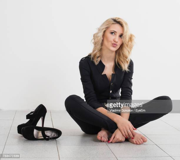 young woman sitting on floor against white background - belle femme pieds nus photos et images de collection