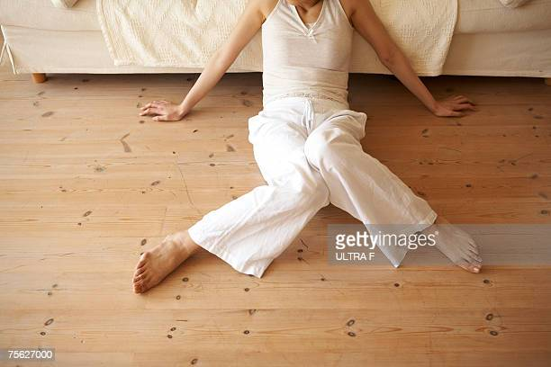 Young woman sitting on floor by sofa in home