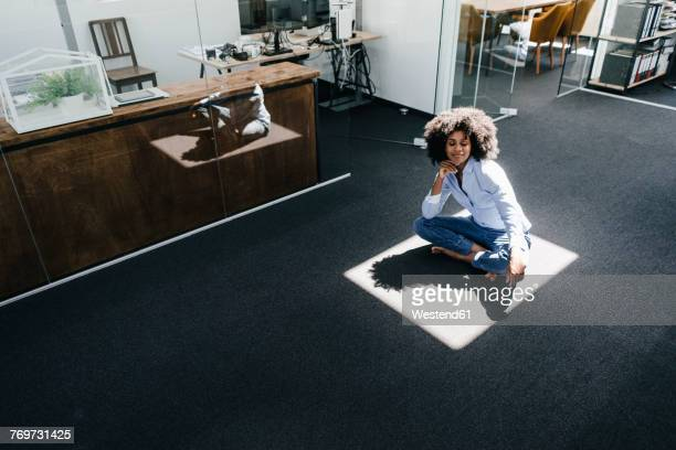 Young woman sitting on floor in office