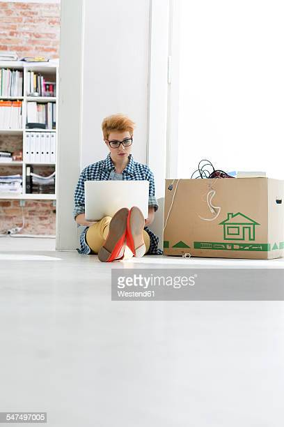 Young woman sitting on floor in office using laptop next to cardboard box
