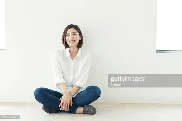 young woman sitting on floor - cross legged stock pictures, royalty-free photos & images