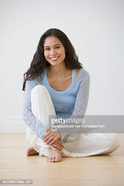 Young woman sitting on floor, portrait