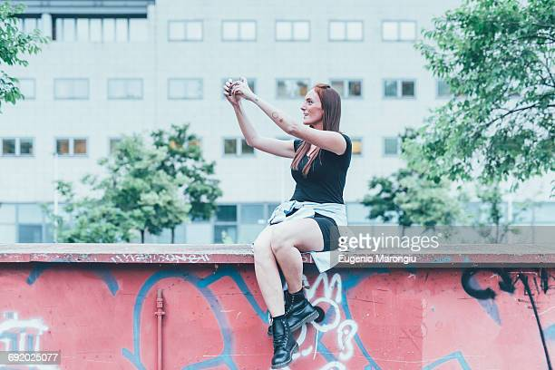 Young woman sitting on graffiti wall taking smartphone selfie
