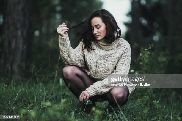 Young Woman Sitting On Grass Against Trees