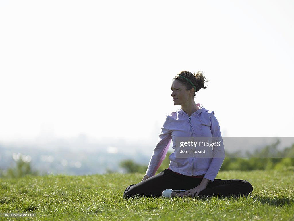 Young woman sitting on grass doing yoga : Stock Photo