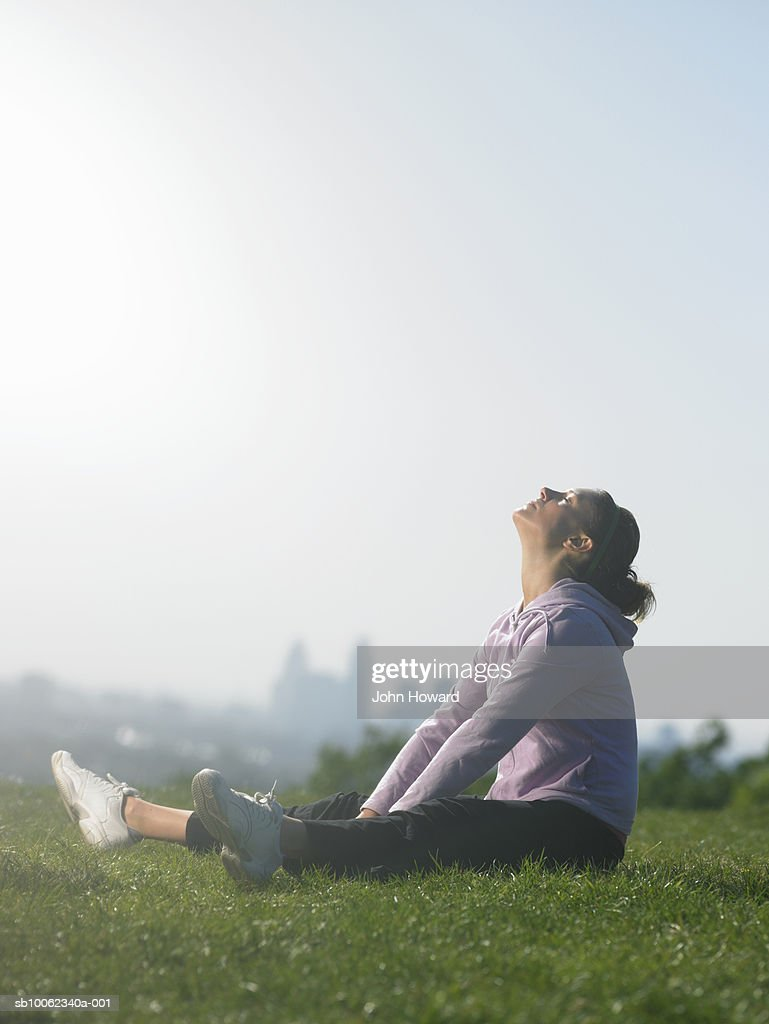 Young woman sitting on grass in park, stretching : Stock Photo