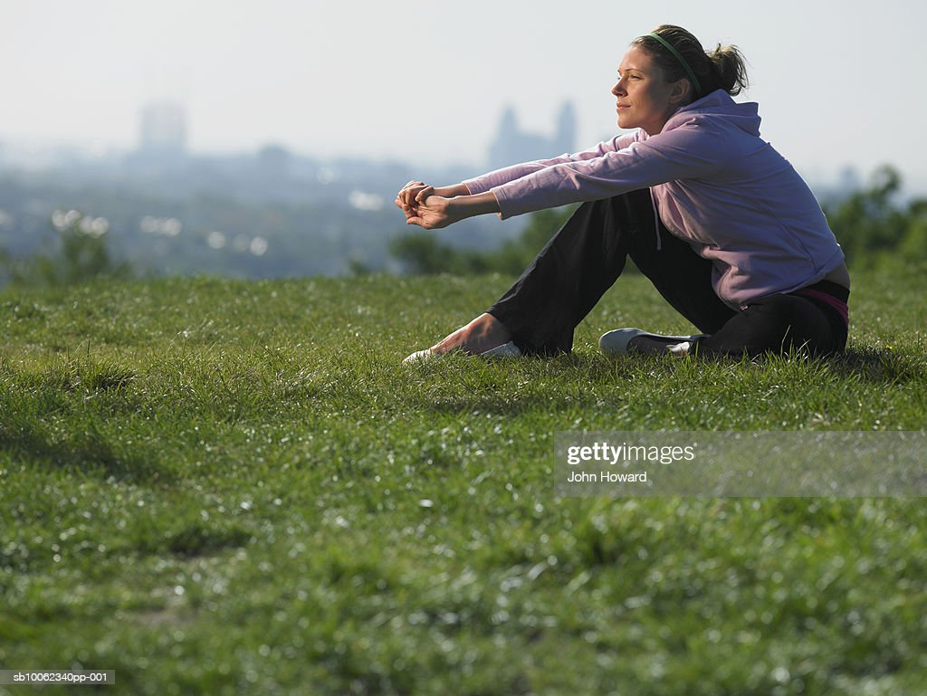 Young woman sitting on grass in sport clothes, cityscape in background : Stock Photo