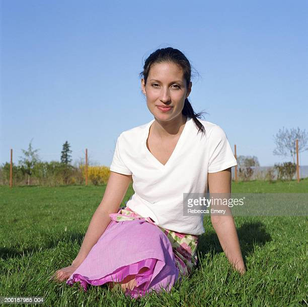 young woman sitting on grass, smiling, portrait - emery stock photos and pictures