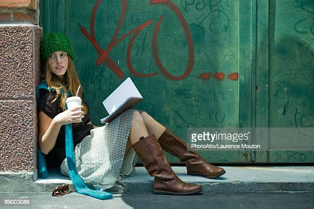 Young woman sitting on ground with book and drink, looking away