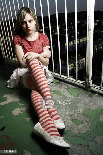Jeune femme assise sur Grunge balcon de l'appartement de nuit