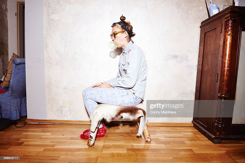 Young woman sitting on hassock wearing sunglasses and blowing bubblegum : Stock Photo