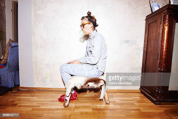Young woman sitting on hassock wearing sunglasses and blowing bubblegum