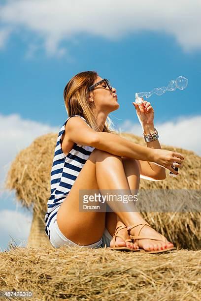 Joven mujer sentada en heno fardos y soplando burbujas