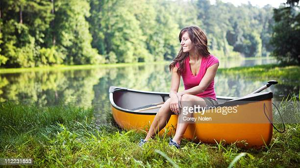 young woman sitting on her canoe waiting to go out onto the water at a lake in oak mountain state park, pelham, al. - pelham alabama stock pictures, royalty-free photos & images