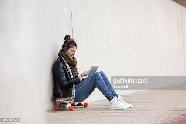 Young woman sitting on her longboard with digital tablet hearing music with headphones