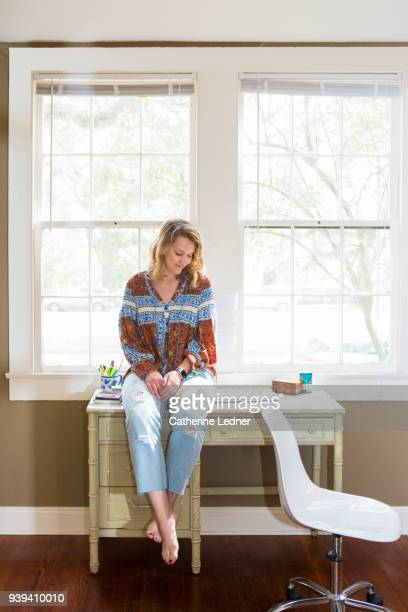 Young woman sitting on home office desk.