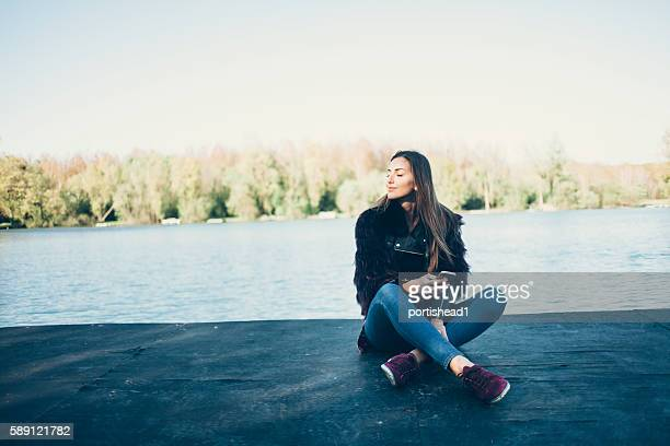 Young woman sitting on jetty and using smart phone