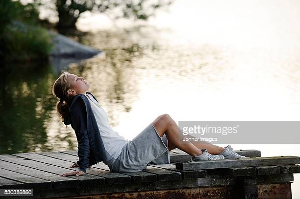 Young woman sitting on jetty