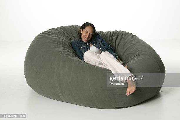Young woman sitting on large bean bag, portrait