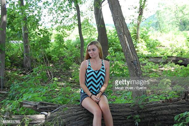 Young Woman Sitting On Log In Forest