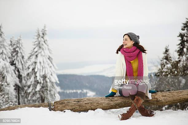 Young woman sitting on log in snow