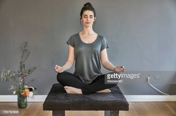 young woman sitting on lounge doing yoga - meditieren stock-fotos und bilder
