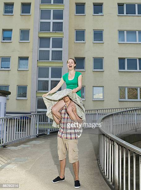 young woman sitting on mans shoulders - carrying a person on shoulders stock photos and pictures