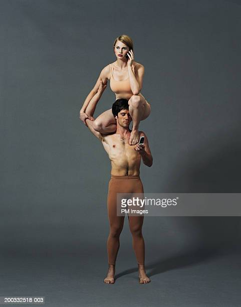 Young woman sitting on man's shoulders talking on mobile phone