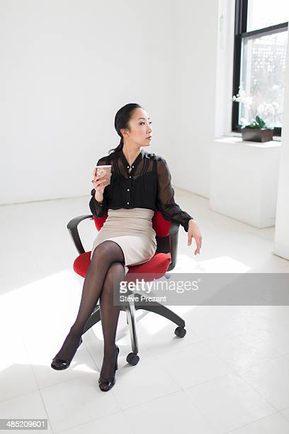 Young woman sitting on office chair with coffee