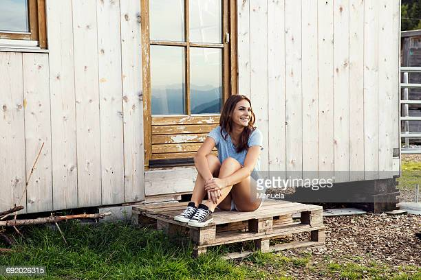 Young woman sitting on pallets outside chalet, Sattelbergalm, Tirol, Austria