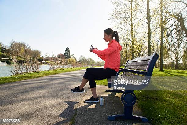 Young Woman Sitting On Park Bench Checking Activity Tracker