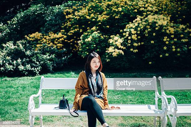 Young woman sitting on park bench, rear view