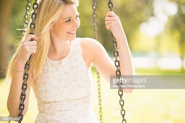 young woman sitting on park swing - bethnal green stock pictures, royalty-free photos & images